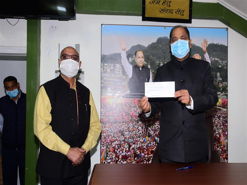 Chief Minister Shri Jai Ram Thakur being presented a cheque of Rs 51,000 by Deepak Dhir of Rajgarh of Sirmour district towards CM relief fund at Shimla on 29 Sept. 2020